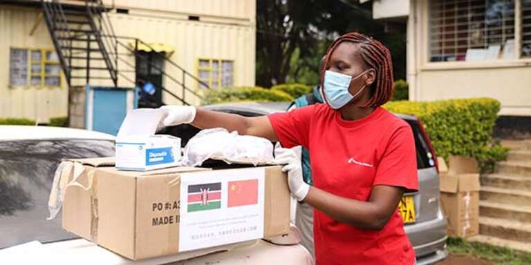 A Save the Children worker in Kenya opens a box of COVID relief supplies to distribute to a local healthcare center. Photo credit: Mark Wahwai / Save the Children 2020.