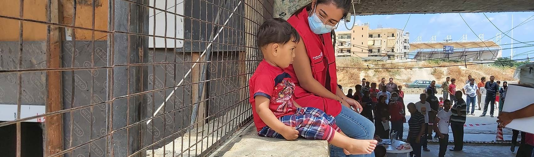 In Lebanon, a health worker wears a face mask while sitting besides a young boy on a ledge overlooking the town.