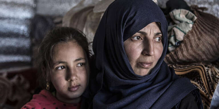 A mother and her daughter huddle close together in a shelter for Syrian refugees in Lebanon.