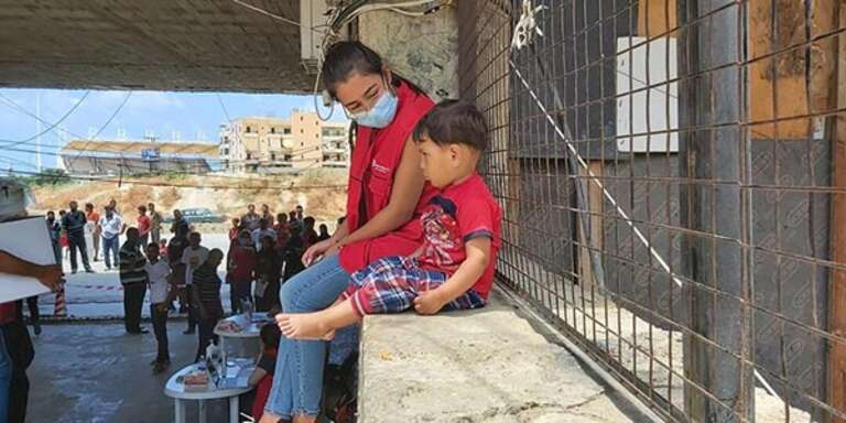 A Save the Children staff member sits with a child on a wall in Lebanon