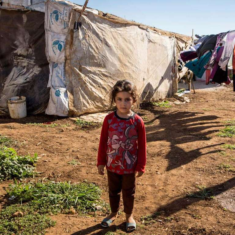 A young Syrian refugee girl stands alone in front of a laundry line and home in a refugee camp.