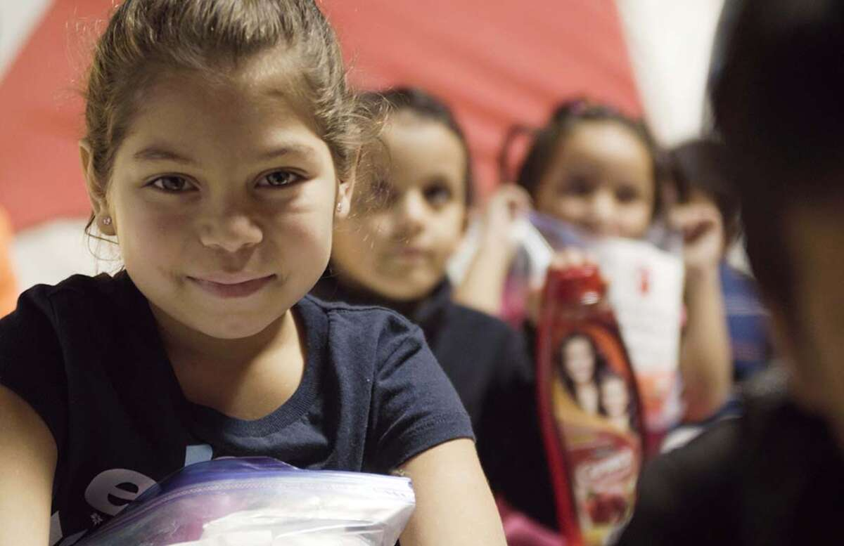 A girl holds a bag of hygiene supplies provided by Save the Children in Mexico.