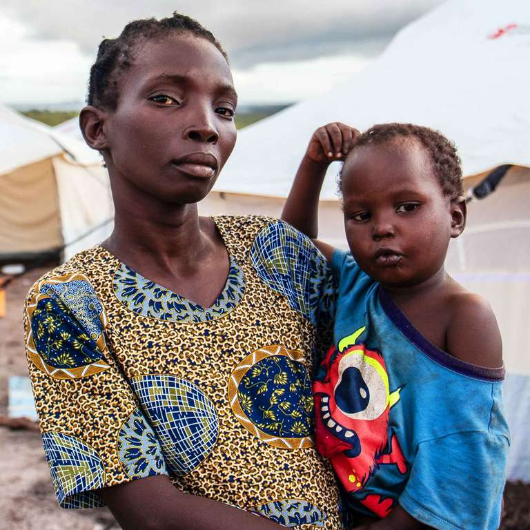 A mother holding her young daughter in her arms stands in front of white tents set up in a temporary camp in Mozambique where Cyclone Idai has caused catastrophic damage. The mother is now desperate for hygiene materials and shelter materials so she and her family can rebuild their home. Save the Children is on the ground helping children and families devastated by the Mozambique cyclone. Photo credit: Sacha Myers / Save the Children, March 2019.