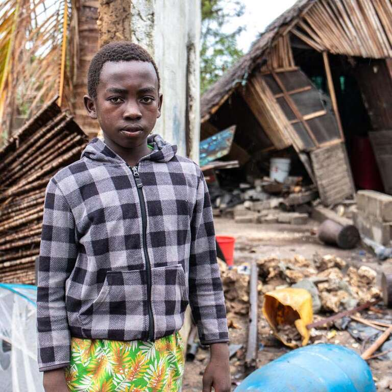 A young boy stands in front of a damaged shelter in Mozambique where Cyclone Idai left a trail of devastation.