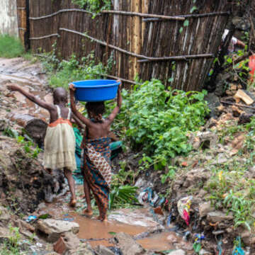 Two young girls, both barefoot and one balancing a large blue basin on her tiny head, step across sharp rocks and muddy water. Next to them is a flattened shelter destroyed by Cyclone Kenneth which struck northern Mozambique on April 25, 2019. Save the Children is scaling up response efforts to provide emergency relief to families and children who have been impacted by this devastating cyclone. Photo credit: Sacha Myers/Save the Children, April 2019.