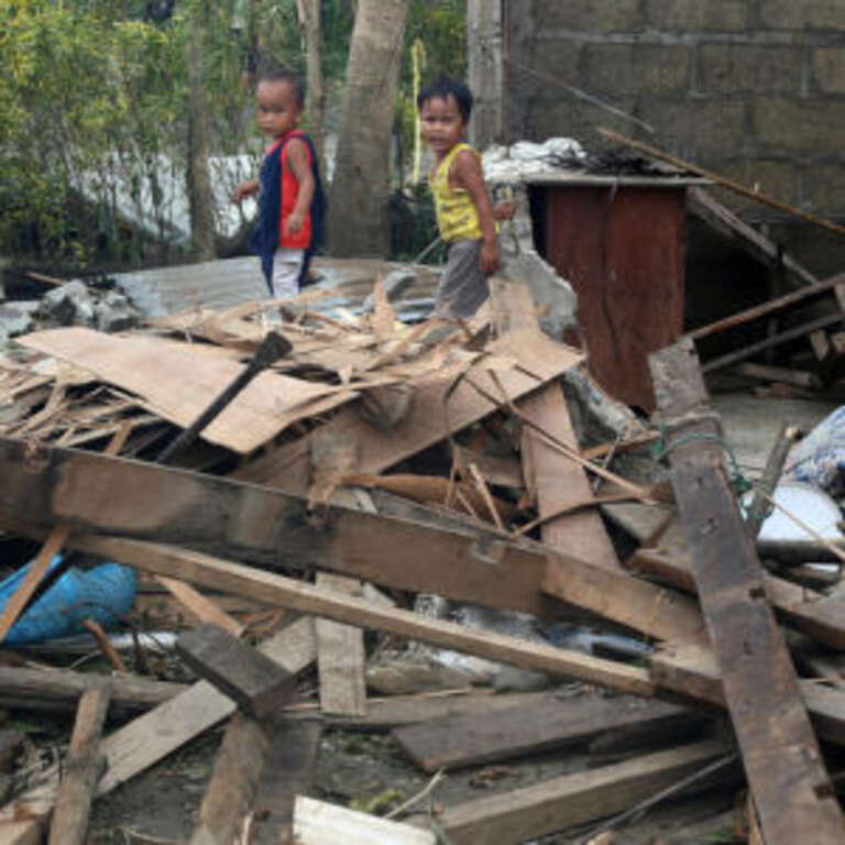Limuel and John Deo walk through debris in what remains of their house after it was blown down by Typhoon Mangkhut. Credit: LJ Pasion/Save the Children