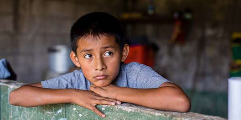 11-year-old Anderson rests his head on his hands while sitting inside his home in El Salvador.
