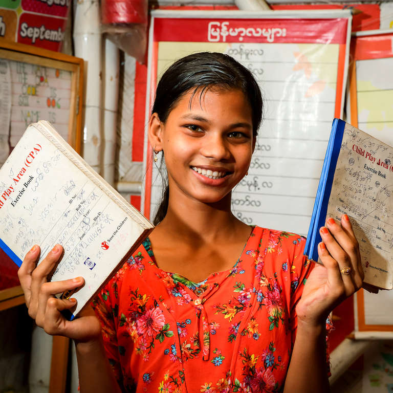 A 12-year-old girl holds up two notebooks at a Save the Children learning center in a refugee camp in Cox's Bazar, Bangladesh. She loves learning English there and being able to make new friends. Photo credit: GMB Akash / Save the Children, June 2018.