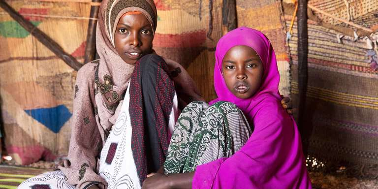 Two sisters, age 7 and 14, sit together in a traditional hut where they currently live in Somalia. The hut was built by their mother and houses the whole family, all of whom were displaced from their home due to drought. The family is struggling to eat, as the drought nearly wiped out their livestock. Save the Children is providing emergency food for the family and other families in Somalia who have been impacted by the drought. Photo credit: Kate Stanworth / Save the Children, July 2019