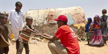 A Save the Children staff member visits children in a village in Somalia where drought has devastated crops and forced many families to be displaced. More than 1.5 million people have become internally displaced in Somalia since November 2016 as a result of drought, conflict and flooding. Photo credit: Marieke van der Velden / Save the Children, April 2019.