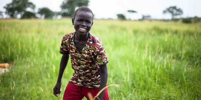 A 10-year old boy smiles as he plays and enjoys a sunny day in a field in a camp for internally displaced people in central South Sudan. Save the Children is working to trace the boy's mother from whom he was separated from when gunmen attacked their village. Photo credit: Martin Kharumwa / Save the Children, Dec 2017