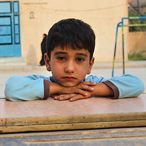 A 5-year old boy rests his head on his folded arms as he sits at a desk. In the background is a school building, currently being used as a shelter to house displaced families in Northeast Syria. The escalation of violence in this area has led to the displacement of approximately 210,000 people, with additional indications of people on the move. Photo credit: Save the Children, Oct 2019.