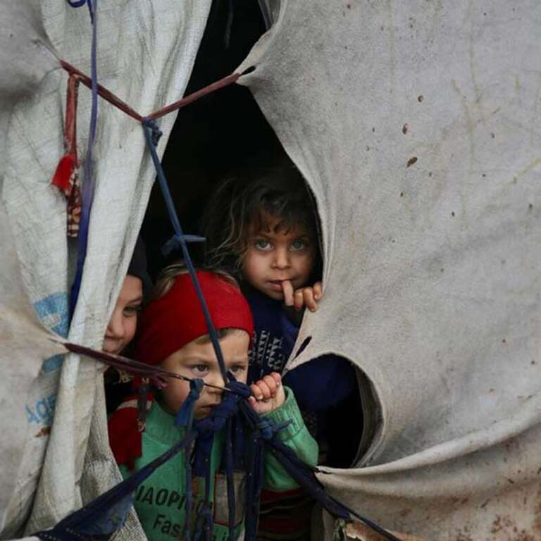 Three small children look out of their family's tent in a displacement camp in Idlib, Syria.