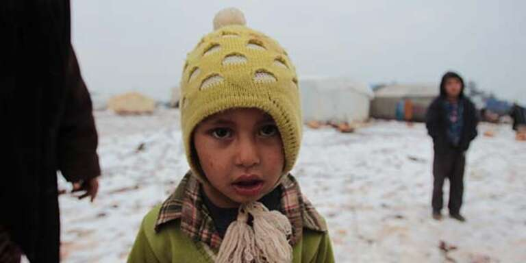 A boy in a yellow hat and green sweater stands in a snow-covered displacement camp in North West Syria.