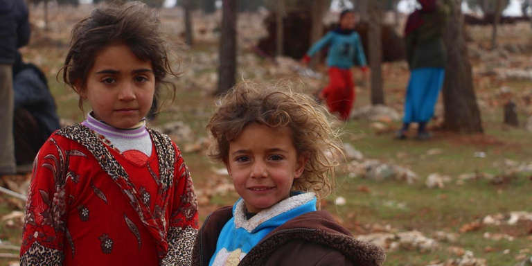 Two young girls in Syria stand together and look at the camera.