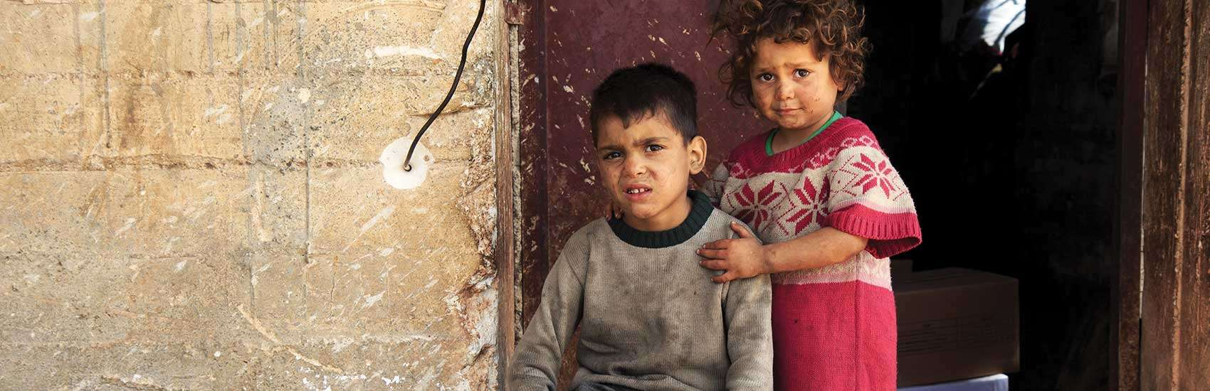 Siblings Mustafa*, age 5, and Fatima*, age 3, lean against the battered doorway of their family's temporary shelter in the suburbs of Idleb, Syria where they have been living for few months. The family was forced to flee their home due to violence and heavy bombardment. The building used to be a coal store so the children are constantly covered in black coal dust. Photo credit: Ahmad Baroudi | Save the Children, May 2015.