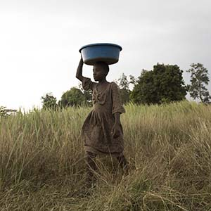 A girl carries a bucket of animal food over her head.