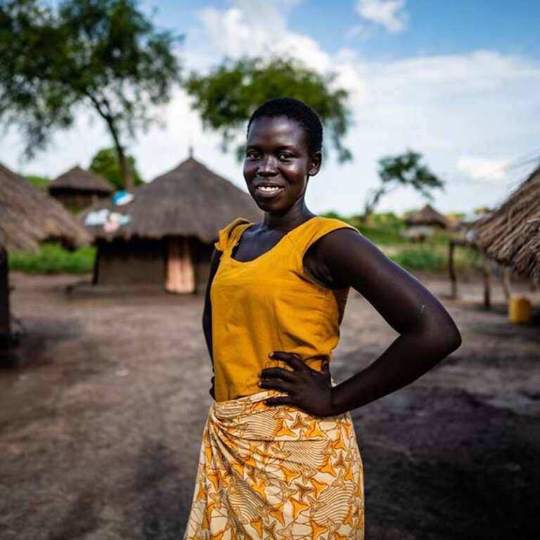 A 14-year-old girls stands with her hands on her hips while smiling in a refugee settlement in Uganda.