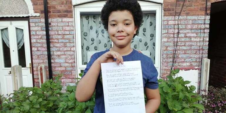 Lincoln, 11, holding a poem he wrote about Coronavirus outside his home in Sheffield, UK.