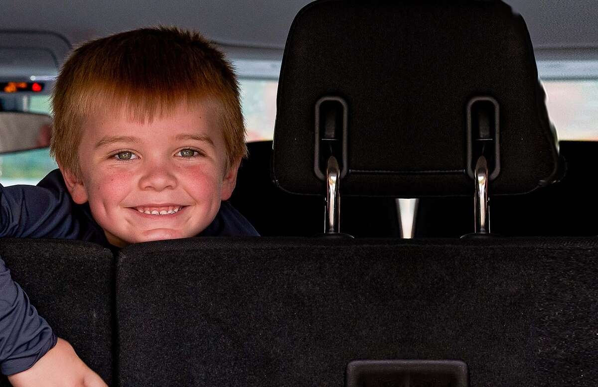 A boy smiles while looking out the back of a car while receiving food during COVID-19.