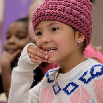 – A girl touches her hands to her mouth while listening intently with other students in her classroom.