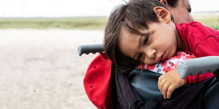 A migrant child lays on the shoulder of a family member
