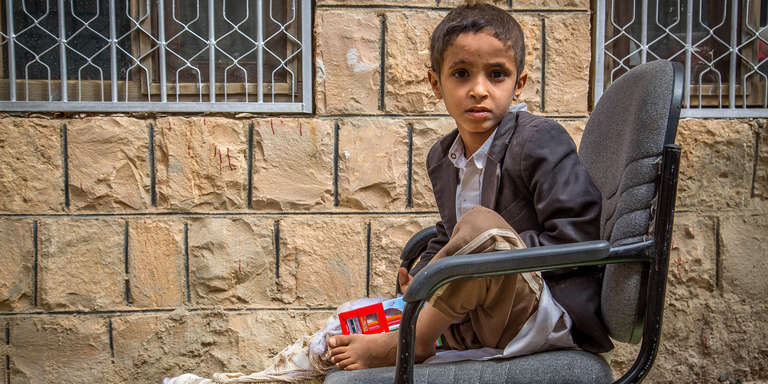 A young boy named Ismail sit on a chair outside a brick building with bars on the windows. The boy's right leg is wrapped, from his toe to above his knee, in white bandages. The boy was on a school bus, riding through Yemen when his bus was bombed by an aircraft belonging to the SLC (Saudi-Led Coalition). Save the Children's Stop the War on Children campaign draws attention to children living in conflict and calls on world leaders to take action to protect children living in war zones. Photo credit: Mohammed Awadh / Save the Children, Sept 2018.