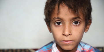 An eight-year old boy is pictured sitting inside a home in Yemen. The boy was on a school bus riding through Saada, Yemen, when the bus was bombed. 40 children under the age of 10 were killed. He survived but not without significant injuries. He had shrapnel fragments next to his eye, in his leg and in his little toe. His foot was broken. Save the Children helped provide the boy with medical care and now, his physical injuries have healed. Since May 2015, through donor support, Save the Children has reached more than 2 million children with lifesaving assistance. Photo credit: Sami M. Jassar / Save the Children, July 2019.