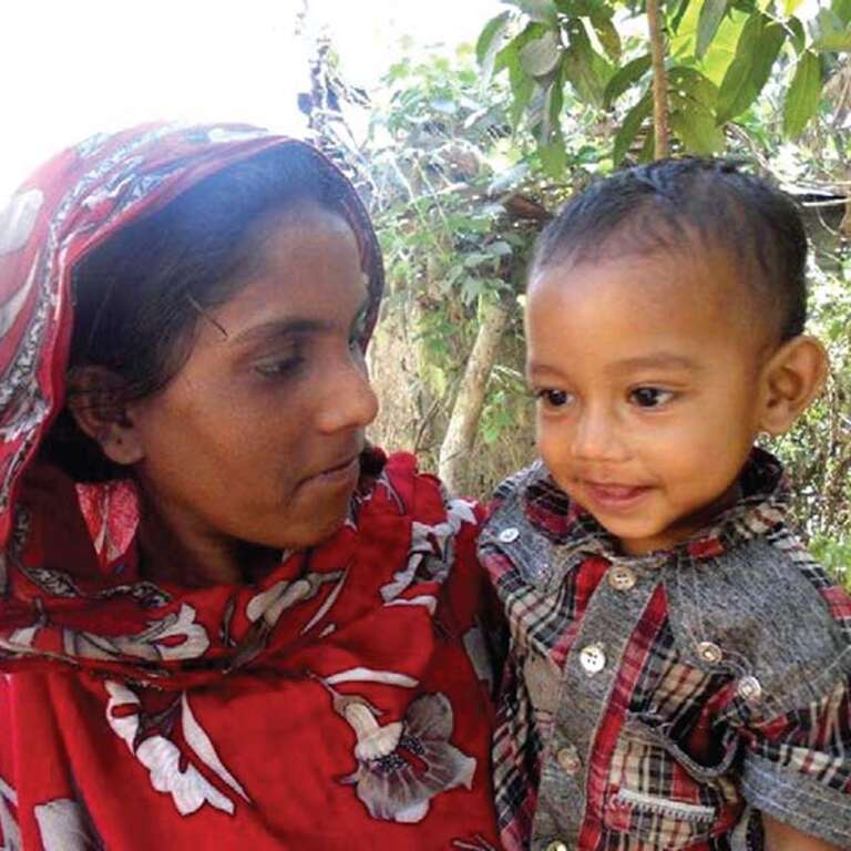 Little Hasabullah with a slight smile on his face is held by his mother in Bangladesh.