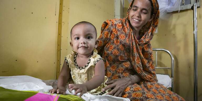 An 8-month old baby smiles while sitting on a hospital bed with his mother in Bangladesh.