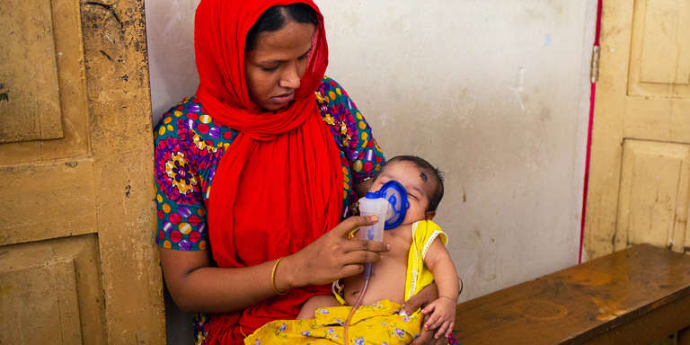 A woman holds a nebulizer for her one month old baby who has pneumonia. They sit in a hospital in Barisal district, Bangladesh. September 2018. Save the Children is helping to train healthcare providers to diagnose and treat pneumonia at the community level. Photo credit: Save the Children / September 2018