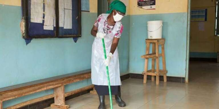 A woman cleans the floor of a health center while wearing gloves, an apron and a mask.