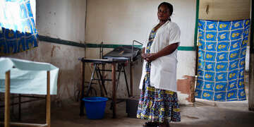 Bossello Menama Patience, 38, a midwife, stands near a bed at a mission hospital in Yusuku Kisangani, Democratic Republic of Congo. She received training through our Maternal and Child Health Program. Photo credit: Kate Holt/MCSP 2017.