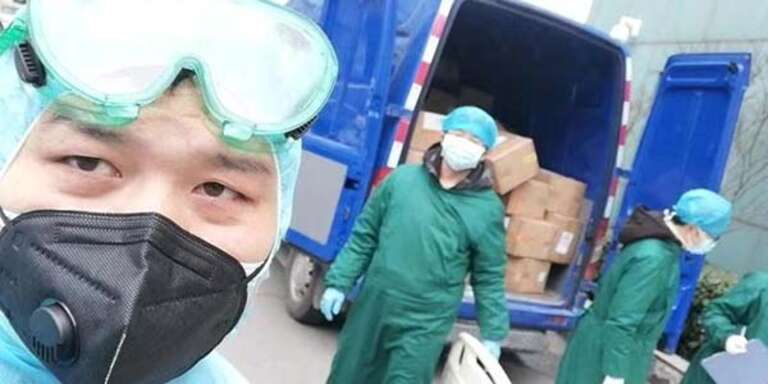 Local volunteers in Wuhan, China wear protective suiting while helping to load boxes of face masks donated by Save the Children onto a distribution truck.