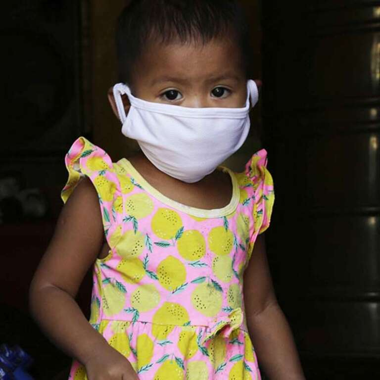 A 1-year old girls wears a face mask during a Save the Children Coronavirus response hygiene distribution in the Philippines.