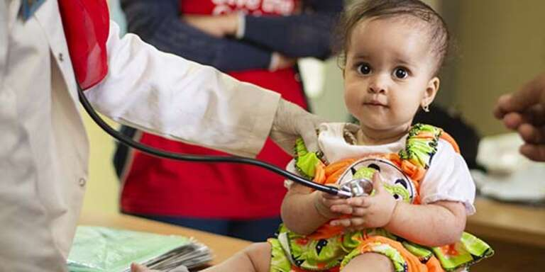 A baby girl receives a check-up at a medical caravan.
