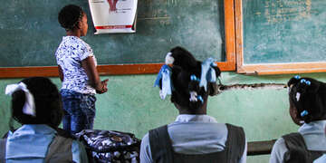 Julienne teaches a classroom of young girls about reproductive health.