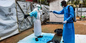 A health worker in a blue gown applies Highlight, a blue dye, to a fellow worker to decontaminate their protective garments from Ebola.
