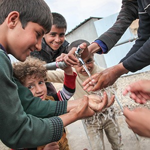 A group of children wash their hands with a water from a Save the Children-constructed treatment plant that turns dirty river water into clean drinking water.