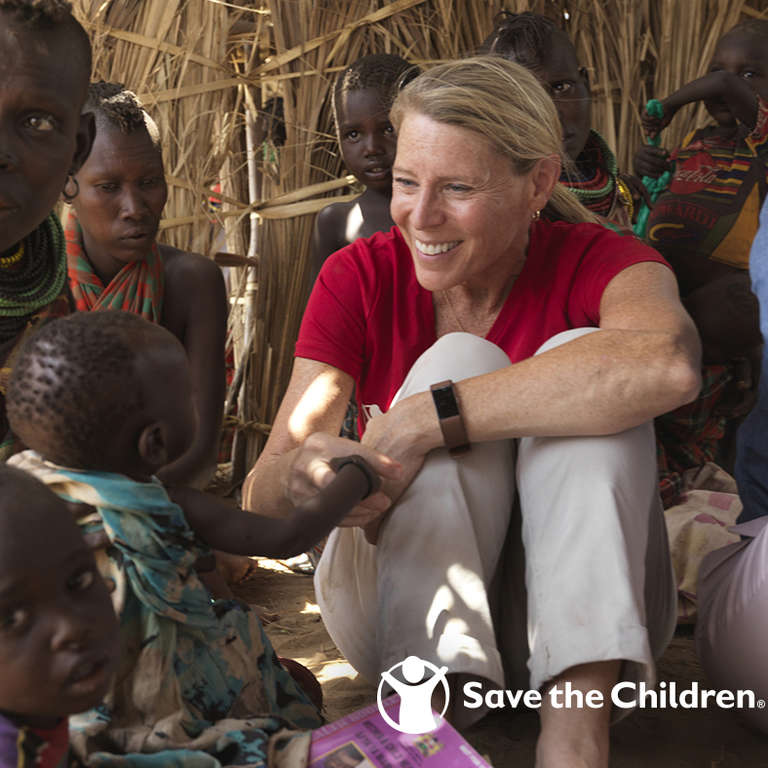Carolyn Miles, President & CEO of Save the Children sits on the floor surrounded by children and mothers in the drought-affected area of Turkana County, Kenya. Wearing a red branded shirt and a smile, Carolyn holds the hand of a young child who looks up at her. Photo credit: Peter Caton | Save the Children, July 2018.