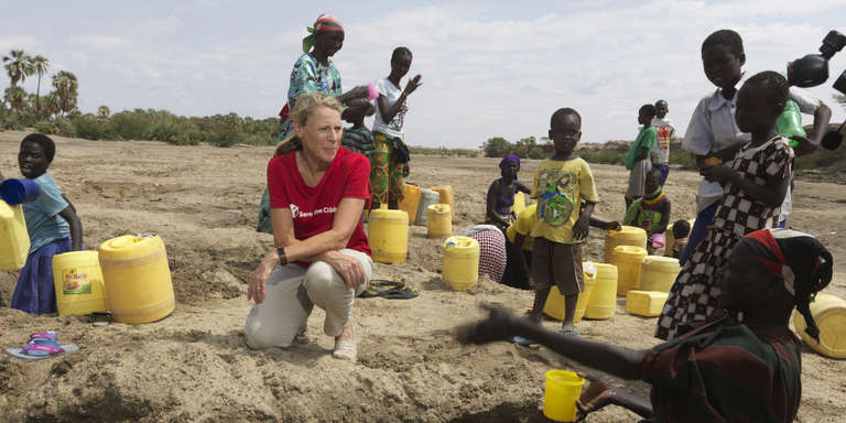 Save the Children President & CEO Carolyn Miles kneels in the dirt in Kenya to listen the stories of mothers affected by the drought in Turkana County, Kenya. Photo credit: Peter Caton | Save the Children, July 2018.