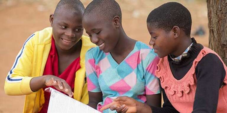Three girls in Malawi read a book together.