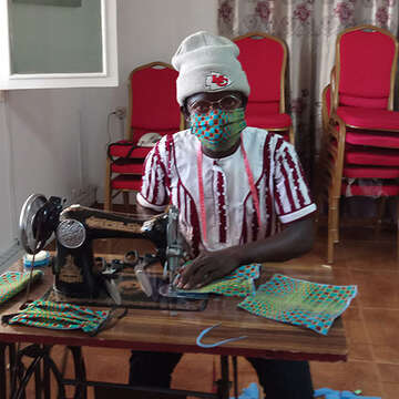 A woman in Mozambique using a sewing machine to stich a face mask to help her community prevent the spread of coronavirus