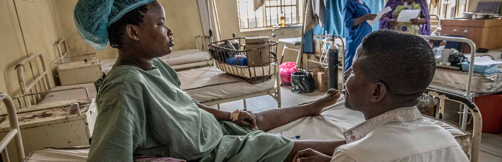 A woman wearing a blue hospital gown sits on a hospital bed in the maternity ward and looks straight ahead while a doctor sits beside her. Other female patients at the Okene Zonal Hospital in Nigeria can be seen in the background along with several white hospital beds. Many of the doctors at this hospital are on strike. The maternity ward use to be very busy but with the doctors on strike this state hospital is practically empty. Photo credit: Save the Children 2020.