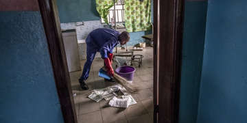A hospital worker wearing blue scrubs cleans the maternity ward with a short broom and a purple bucket. The hospital is in Nigeria.