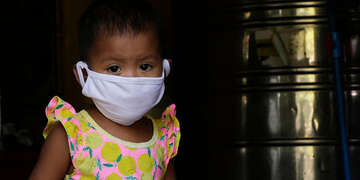 A 19-month old girl wears a cloth face mask while standing next to a water refilling station that her parents operate in the Philippines.]