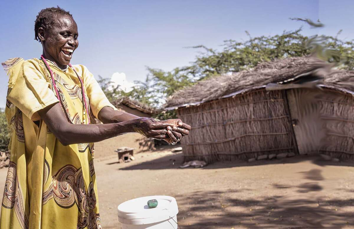 A woman in South Sudan washing her hands outdoors to prevent against the spread of COVID-19.