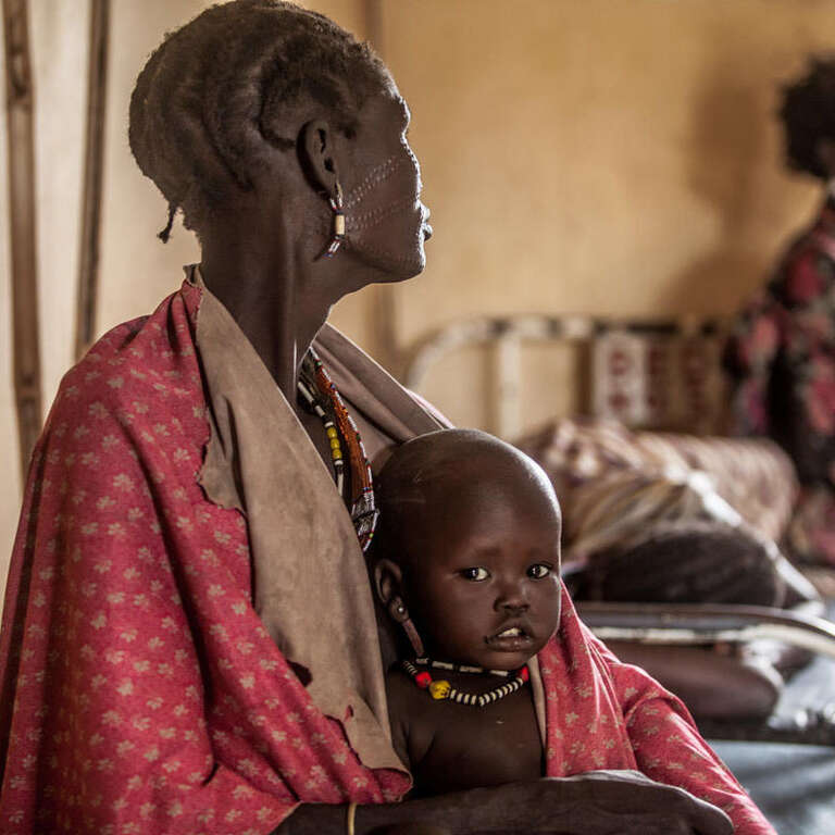 One year-old Hakaroom sits with his mother Lokuru at a Save the Children supported health centre in Kapoeta, South Sudan, after being treated for severe pneumonia