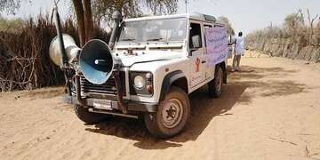 Save the Children Land Rover all terrain vehicle 4x4 with large megaphone spreads awareness messaging about COVID-19.