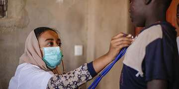 A Save the Children community doctor wears a face mask while holding up a stethoscope to a young boy in Sudan.]